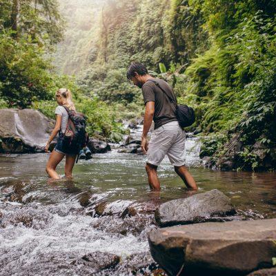 Couple walking across the stream.