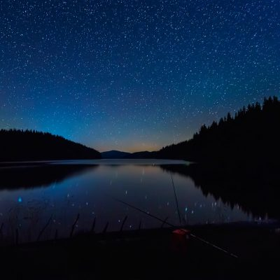Starry sky above mountain lake
